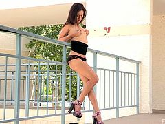 Daring Arianna walks around her hotel building fully nude then she sits down and fingers her shaved pussy right there in public.