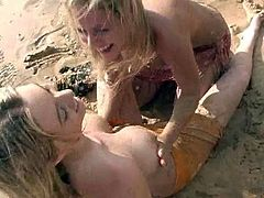 Curvaceous babes have fun on the beach. These stunning babes touch each others big boobs and swim in a sea.