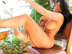 Captivating brunette Romi is having fun indoors. She kneads her big natural boobs and then touches her nipples with her toes.