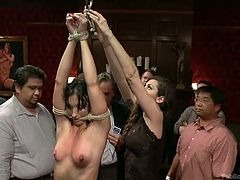 Sexy milf Wenona gets rope around her arms and through her mouth then her arms are hung from the ceiling so she has to stand on her tiptoes. She is hung upside down and then the group of men take turns putting their dicks in her mouth.