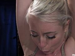 This blonde slut gets tied with rope and her arms are hung from the ceiling. She gets electrodes hooked up to her nipples and then her redheaded mistress controls the intensity. Her mistress sticks her feet in the blonde's face.