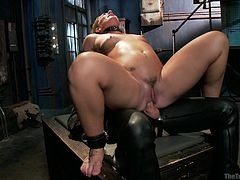 This dirty whore has a collar around her neck and two around her ankles so she can't go anywhere. She has just enough space to bounce up and down in the leather clad gimp's cock. She is fucking him so hard that she is working up a sweat.