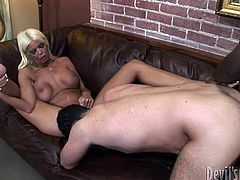 The wife fucks her husband with red strapon on the sofa.