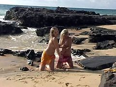 Touch yourself watching these blonde babes, with immense tits and nice asses, while they pose erotically for the camera covered in sand.