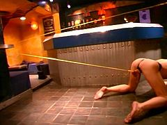 Nasty brunette mistress in her intense torturing fun as she overpowers submissive muscled hunk in the club.