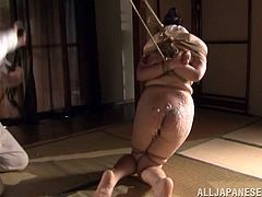 Entertain yourself by watching this Japanese brunette, with natural boobs and a nice ass, while she gets tied up hard and tortured.