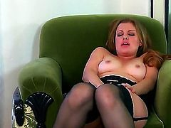 Sovereign Syre sits in her green chair and wears black stockings to look more sexy while she rubs her cunt with her small hands.