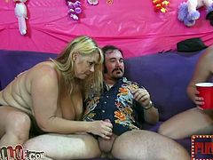Three big boobed and perverted blondies serve one lucky guy by blowing in turns and beating his cock all together at the same time.