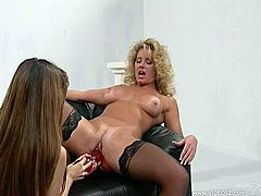 Johnni Black and Alex Dane are two sizzling MILFs in leather lingerie and stockings. They have a memorable lesbian sex. Chicks lick and finger each others pussies. They also use a huge red dildo and a strapon.