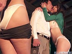A pretty babe gets tied up to a wooden post. She gets her tits licked and fondled by a couple. Then this couple have sex in standing up position. The tied up girl has to watch.