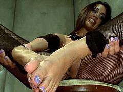He has to lay on the ground, like a little slut and she sits in the chair, and lords over him, like the cruel goddess, that she is. Watch, as she puts her feet into his mouth and the other foot onto his cock. She makes him lick the sweat off her soles and toes, before giving him a footjob as a reward.
