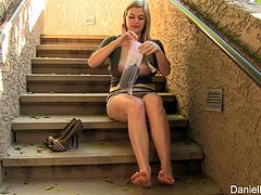 Danielle likes to have fun so she sat down in a public stairwell, lifted up her skirt and put on a glove as she rubbed her pussy.