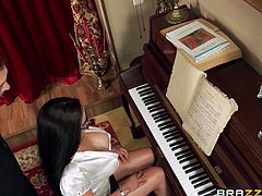 The instructor can't keep his eyes off the massive melons of his student. As he shows her the proper technique for tickling the ivories, he gets a raging boner. Before long her big breasts are bursting out of her shirt, and she is on her knees sucking his pecker.