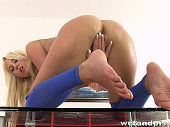 Naughty Carla Cox takes off her pantyhose. She pees in a glass lying on a table. Carla also fingers and toys her pussy.