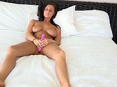 A beautiful solo model shows her nude body lying on a bed. This hot girl with juicy boobs toys herself with her favorite vibrator.