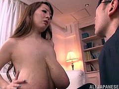 Sexy long-haired Japanese milf is having fun with a guy indoors. She takes her bra off and demonstrates her massive natural jugs to the dude and lets him knead them.