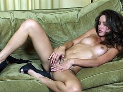 Have a blast watching this brunette doll, with natural jugs wearing high heels, while she masturbates lying on a couch in a solo model video.