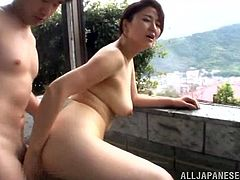 Get excited watching this Asian cougar, with big knockers and a hairy pussy, while she gets nailed hard and moans like a horny Japanese MILF.