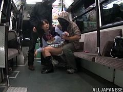 This crazy Japanese girl gets down with these two guys as she sucks and fucks them both while they ride on a public bus across town.