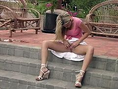 A gorgeous blonde babe sits on the stairs with her legs opened. She lifts up a skirt and plays with her shaved pussy. In addition Alison shows off her hot ass.
