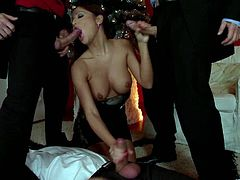 Gorgeous porn star with lovely fake tits gives a blow job as she strokes two cock giving them a fantastic hand cob until they cum in her mouth