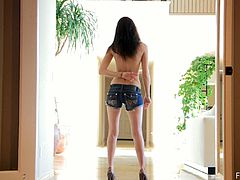 Tall brown-haired girl called Kiara, wearing shorts, is getting naughty in the hallway. She shows her nice body for the camera and kneads her small boobs.