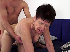 Masturbate as you watch this short haired granny, with big tits wearing big panties, while she gets nailed hard over a blue coach.