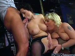 Two horny MILFs with huge boobs have a hot threesome sex in the empty bar. They lick each others boobs and get banged.