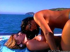 Take a nice look at these babes, with natural boobs wearing bikinis, while they touch and lick each other ardently outdoors in a yacht.