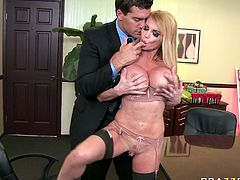 Hussy blonde juggles her big fake boobs in front of her boss. He gets horny and takes out his cock and pushes it deep in her throat while she stands on her knees.