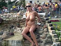 A group of people are having a party on the poolside. Sexy nude blondes demonstrate their bodies to public. The one of the girls hides behind the corner and masturbates her shaved coochie.
