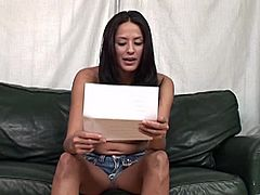 Dude, watch this flamboyant raven-haired enchantress sitting on the black leather couch! She answers some questions demonstrating her nice natural boobies.