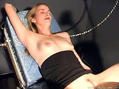 Voracious light-haired hottie wearing black dress lies on the table spreading her legs and gets her moist cooch screwed with mechanical dildo.