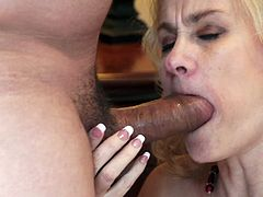 A mature woman with long blonde hair, big natural tits and a shaved pussy enjoys sucking a stranger's massive cock and balls.