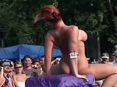 This hot MILF does a sexy strip tease and an erotic pole dance while a group of people watch and cheer her on at an outdoor festival.