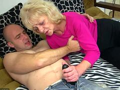 This horny granny strokes a guy wearing a strap-on and enjoys getting her hot pussy drilled by his big black dildo cock.