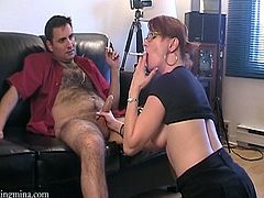 Kinky redhead bitch, wearing glasses, is trying to please a hairy man. She sucks and rubs his weiner ardently and stops only when it explodes with jizz.