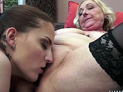 A sizzling hot granny with long blonde hair and massive tits enjoys getting her shaved pussy licked and fingered on her sofa.