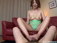 Busty Japanese bitch Nanako Mori, wearing a swimsuit, oils her big natural tits and belly and gives a footjob to a man. Then she lets him cum on her face and enjoys it a lot.