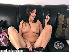 Hot brunette mom, wearing a bra, smokes a cigarette on a sofa. Then she strips and flashes her tits and shaved pussy.