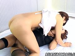 Elegant Japanese brunette in sexy black stockings exposes her round ass and her sweet hairy pussy to her domme. She slams a fat strapon down her cunt long and hard.