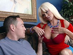 This sexy blonde milf has a giant pair of tits. She shows off her melons to her young friend, and then she kisses him. She licks his cock and slaps his pecker against her tits. His dick goes in between her big boobs and on her lips. Will she let him blow his seed on her?