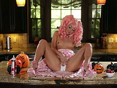 Lovely pink haired porn star with small tits in high heels screams in pleasure as she fingers her pussy erotically in a kitchen.