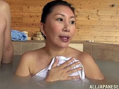 A relaxing bath turns hardcore when this busty Japanese MILF meets a couple of guys and ends up fucking one of them in the tub.
