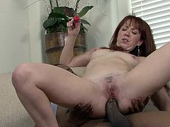 Lewd redhead Trinity Post is having fun with a black stud indoors. Trinity sucks the man's huge fat dick, then lets the guy fuck her butt and fill it with jizz.