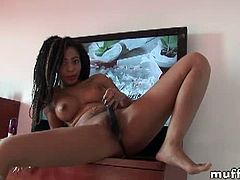 Busty and naughty ebony babe Sandra R. is ready to have some kinky solo action while sitting on the TV. She uses her big black dildo to experience deep orgasm.