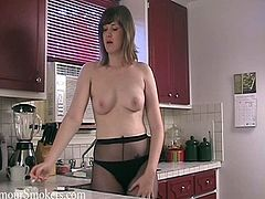Chubby brown-haired woman, wearing pantyhose, is playing dirty games in the kitchen in smoking fetish solo clip. She strips and flashes her boobs and smokes a cigarette seuctively.