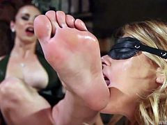 Two hot busty lesbians on high heels punish a blonde milf. Carissa's on knees licking toes. She is blindfolded and her legs and hands are also tied up strongly with rope. Click to watch how she obeys every command like spreading her legs. Her lovely butt gets whipped without mercy until it reddens.