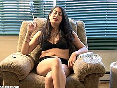 Long-haired brunette milf Madison G, wearing panties and a bra, is sitting in an arm chair indoors. Madison smokes a cigarette seductively and tells about herself.