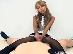This gorgeous Japanese made teases a horny guy as she gives him a sexy footjob and strokes his hard cock while she wears the sexiest uniform.